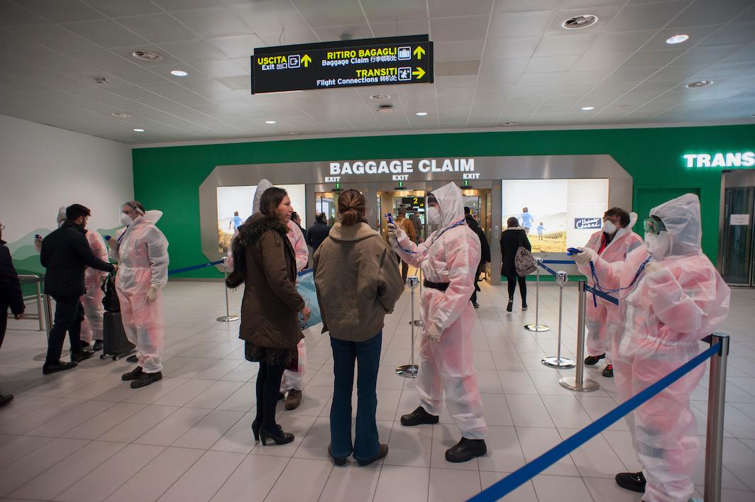 Det är februari 2020 och passagerare på flygplatsen i Bologna testas för covid-19. Med möjlighet att begränsa resandet att WHO kunnat begränsa smittspridningen, anser en panel.