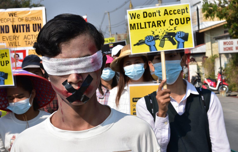 """""""Vi accepterar inte militärkupp"""", står det på plakatet bakom en ung man som på gatan iTaunggyi, i Myanmar, tejpat över sin mun, öron och täckt över ögonen i protest."""