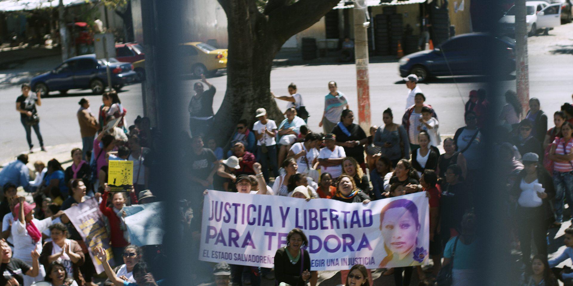 Rättvisa och frihet för Teodora, står det på banderollen utanför domstolen där Teodora Carmen del Vasquez öde avgörs, i San Salvador, El Salvador. Bild från filmen Fly so far.