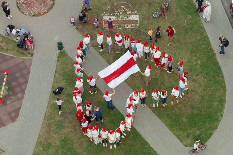 Människor i Belarus formar ett hjärta med en äldre version av Belarus flagga, som regimen förbjudit, i protest mot diktaturen.