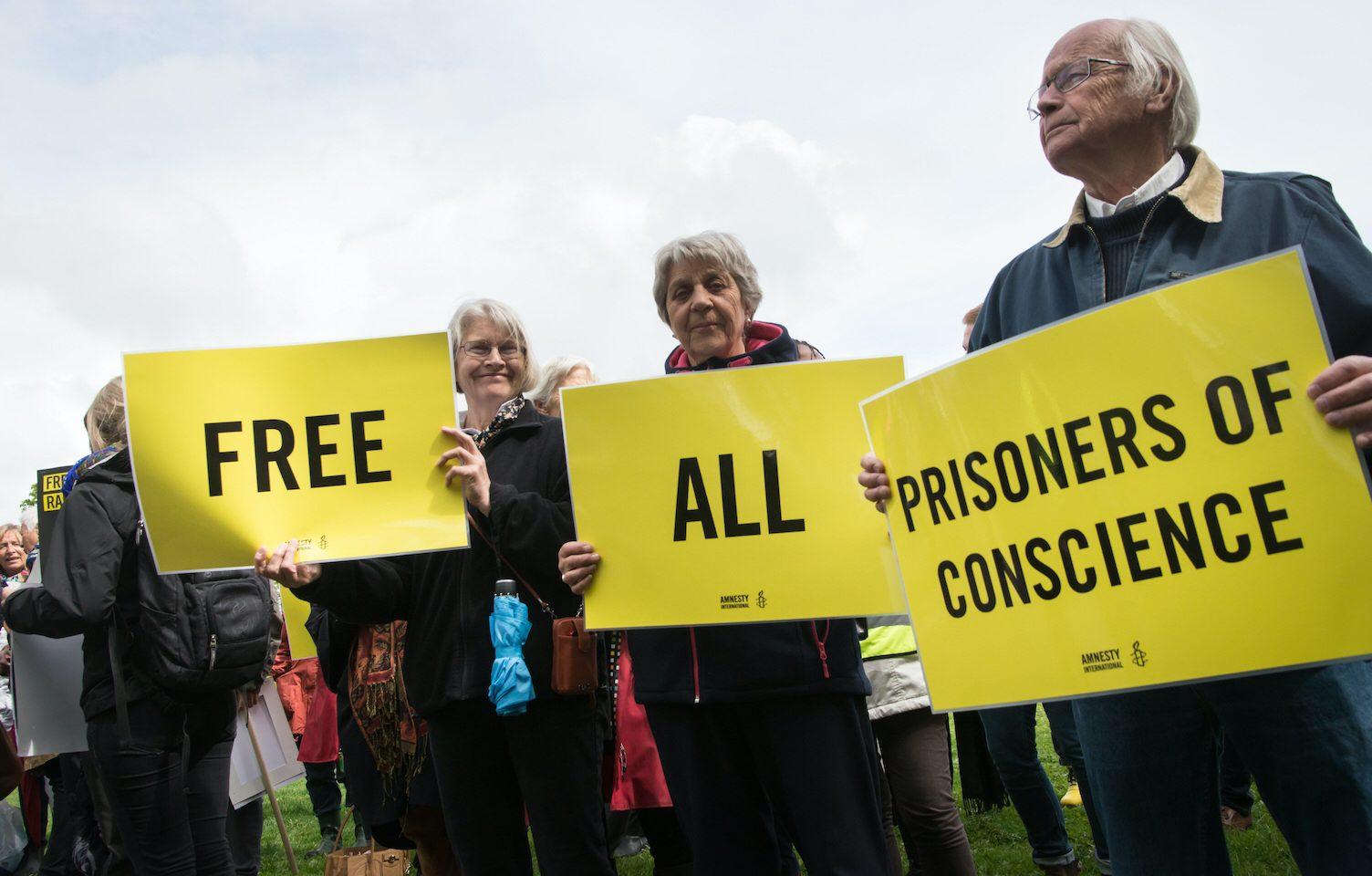 """""""Befria alla samvetsfångar"""", står det på demonstranternas plakat. Amnesty Sverige gör nu besparingar på grund av inställda insamlingskampanjer."""