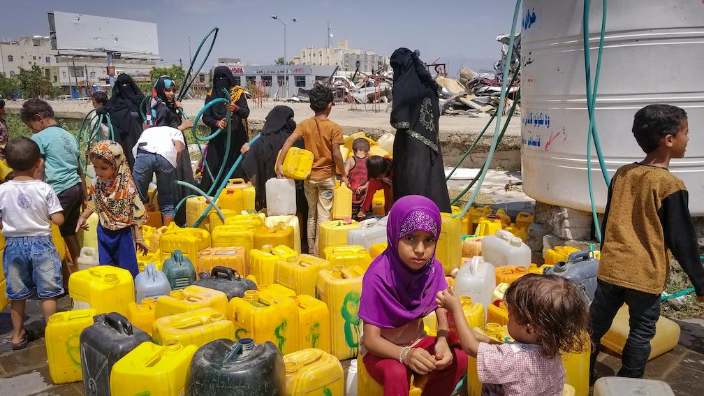 Barn och kvinnor i Taiz City, i Jemen fyller på dunkar med vatten - en bristvara i landet som nu lidit fem år av krig och drabbats hårt av kolera och i värsta fall även corona.
