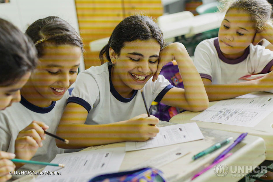 12-åriga Hanan Dacka (mitten) kom från Syrien till Brasilien 2015. Här sitter hon i kolan tillsammans med sina nya brasilianska vänner. Idag får allt för få flyktingbarn tillgång till utbildning.