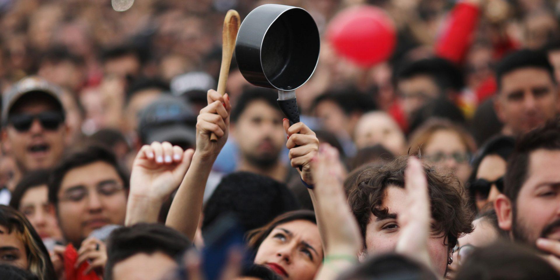 En kvinna bankar på en kastrull, symboliskt för protester i Latinamerika, under en antiregerings-konsert i Santiago, Chile.