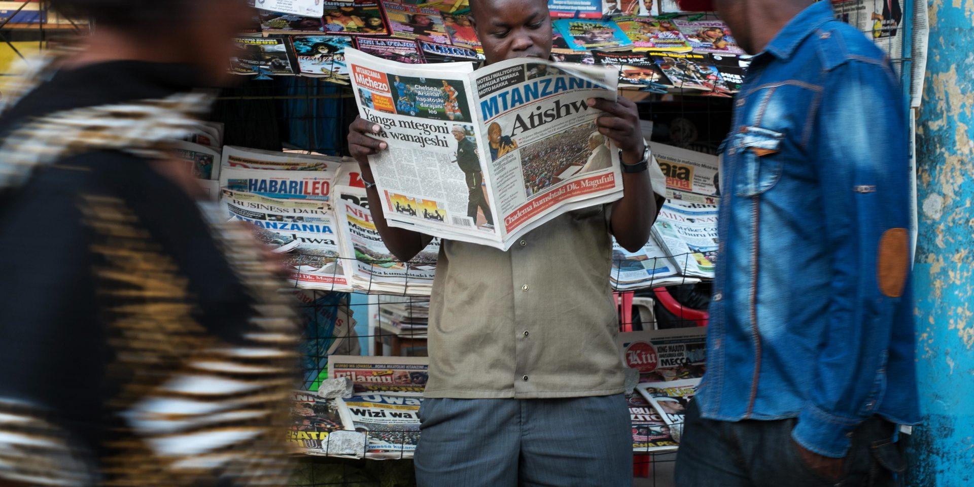"""Det krävs mod för att vara journalist i Tanzania, nya lagar har tryckt tillbaka den fria journalistiken. Här läser Julius Donald en lokal tidning vid sitt tidningsstånd i Mwanza inför valet 2015 som vanns av John """"Bulldozern"""" Magufuli. Sedan dess har pressfriheten minskat rejält i Tanzania."""