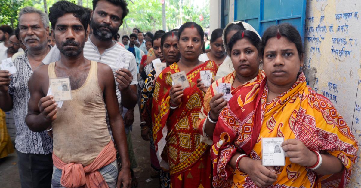 Män och kvinnor står redo att rösta utanför en vallokal i Howrah, Indien, den 6 maj i år. Sammanlagt finns en miljon vallokaler utplacerade i landet.