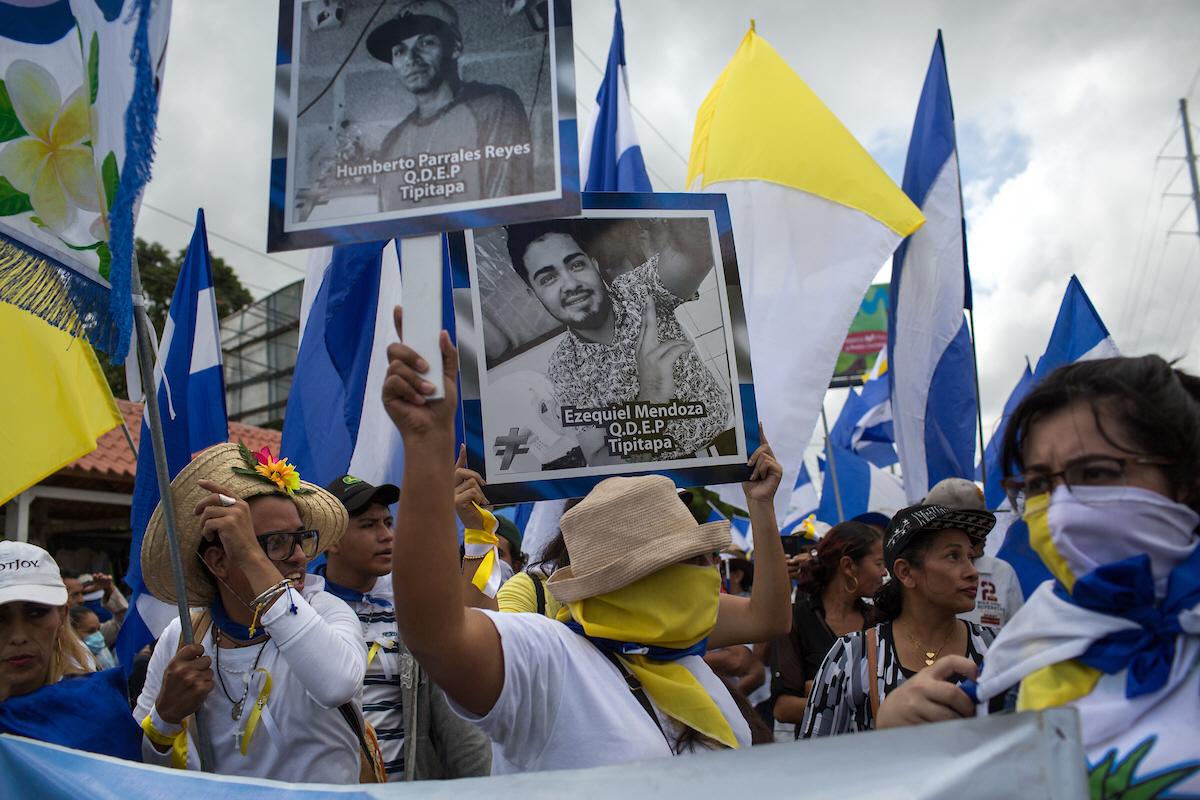 Demonstranter i Nicaragua håller upp bilder på dödsoffer. Álvaro Conrado var det andra dödsoffret under protesterna 2018. För oppositionella demonstranter blev han en symbol för det statliga våldet.