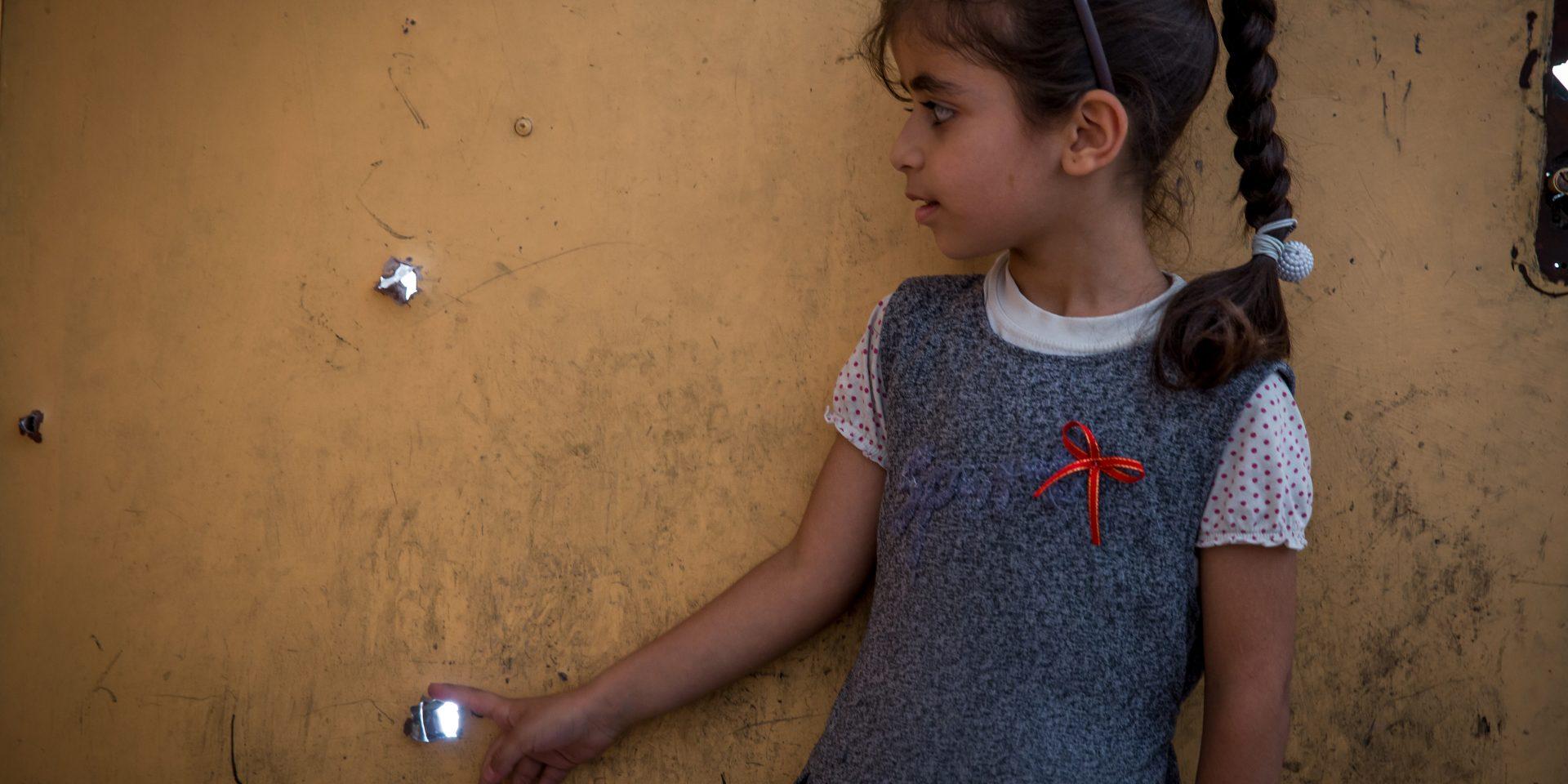 """""""Vårt hus har också sådana här hål"""" säger Abrar och pekar på kulhålen i skolans dörr."""