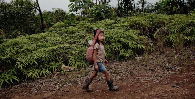 En kichwa-flicka bär sin väska genom skogen i centrala Ecuador.