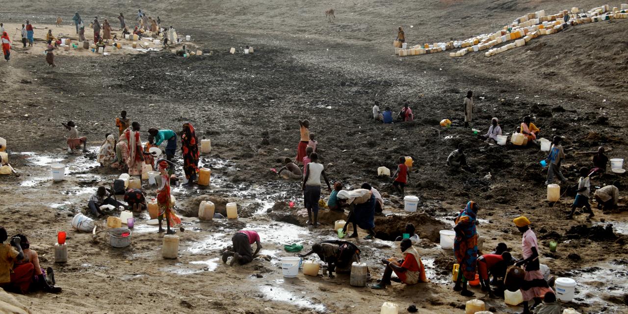 Flyktingar gräver efter vatten i ett upptorkat vattenhål i flyktinglägret Jamam i Sydsudan.
