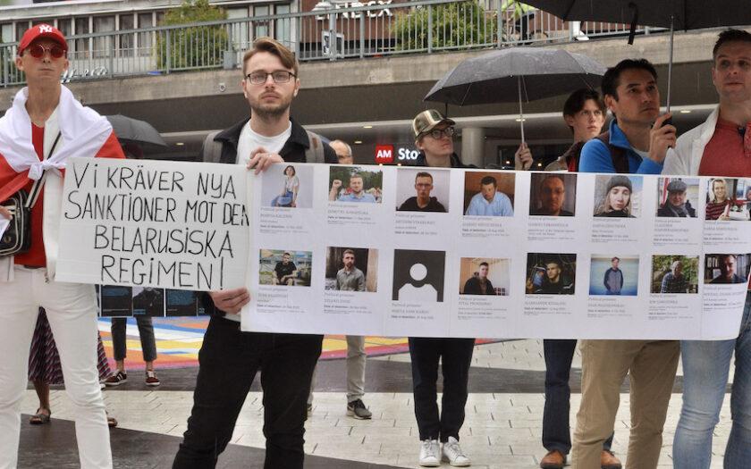 Demonstranter med foton av fängslade belarusier vid manifestation i Stockholm 8 augusti 2021.