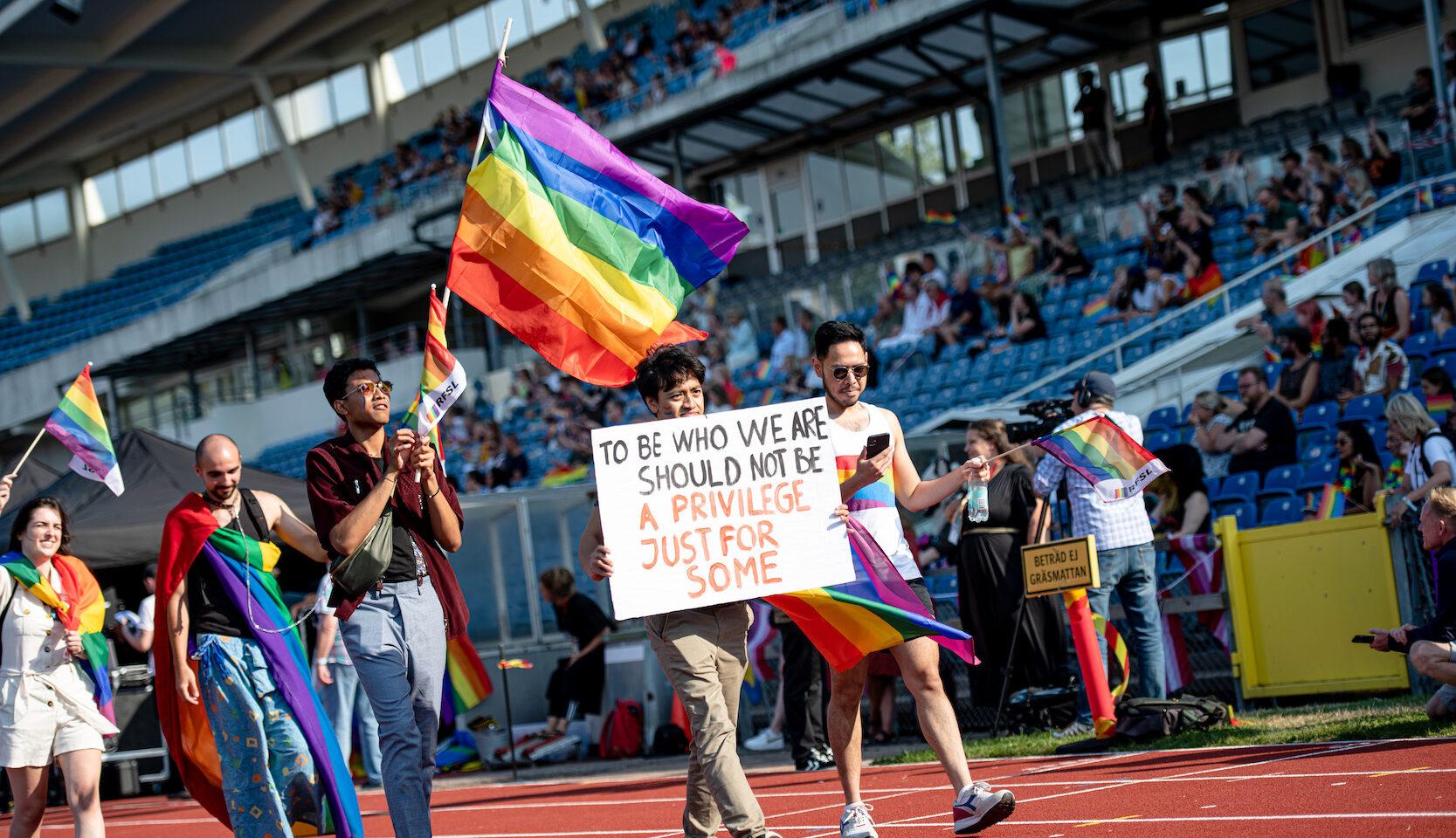 """Invigningen av World Pride på Malmö stadion, """"Att vara dem vi är ska inte vara ett privilegium endast för ett fåtal"""", står det på skylten."""