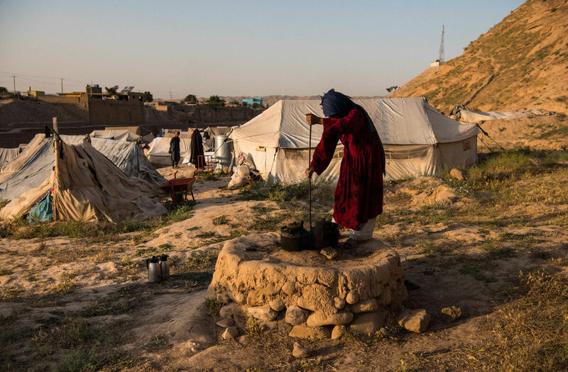 En kvinna i ett flyktingläger i Baghlan, Afghanistan, gör upp eld.