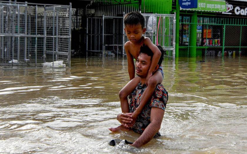 En man vadar med sin son genom översvämningarna som drabbade Phnom Penh i Kambodja år 2020.